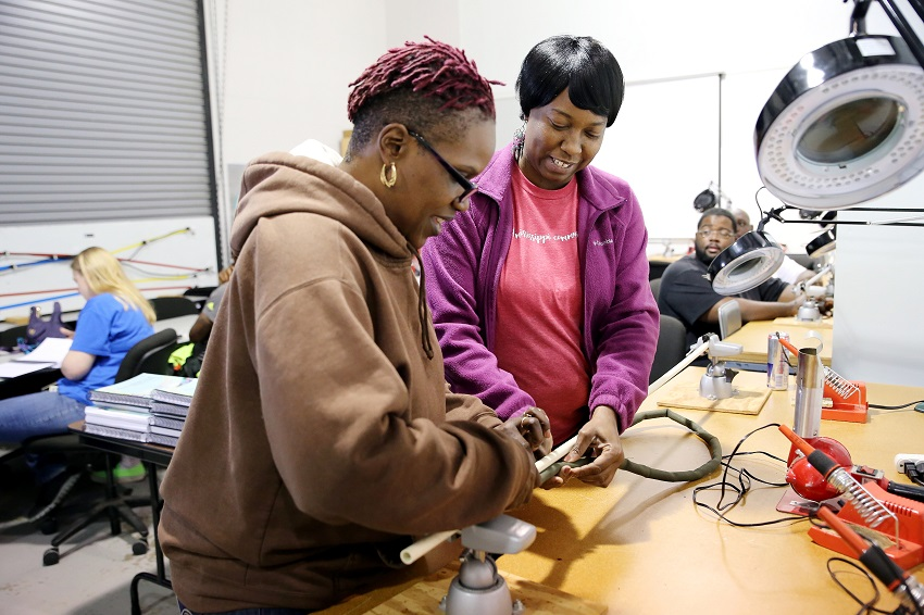 Starkville resident Kim Coats, at left, and Columbus resident Teresa Brooks, work on a cable during an Avionics and Cabling course at East Mississippi Community College. Employees who complete aerospace-related programs at EMCC are in high demand by local manufacturers.
