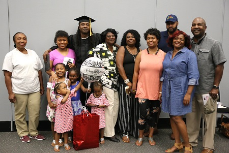 Maben resident Roger Jones, at center, with members of his family following the graduation ceremony for students who earned their high school equivalency diploma through East Mississippi Community College's Adult Basic Education Launch Pad program.